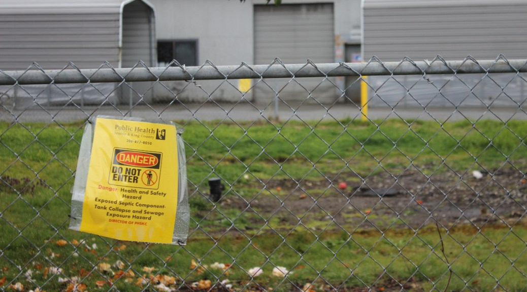 "Photo of chain link fence with a yellow Public Health notice attached to it with text reading ""Danger, Do not enter."""