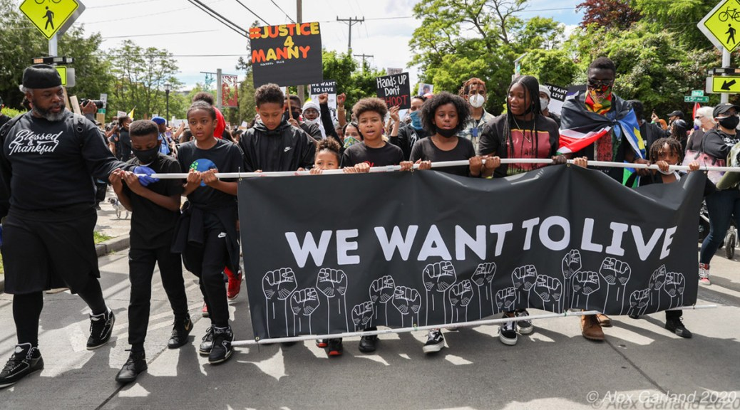 "Black youth protestors carry black banner with white raised fists and text that reads ""We Want To Live."""
