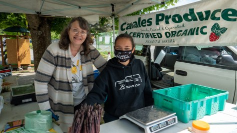 Canales Produce prepares their booth with fresh asparagus at the Columbia City Farmers Market.