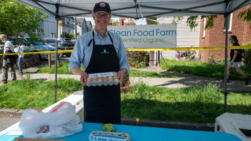 Clean Food Farm prepares their booth with their certified organic eggs at the Columbia City Farmers Market.