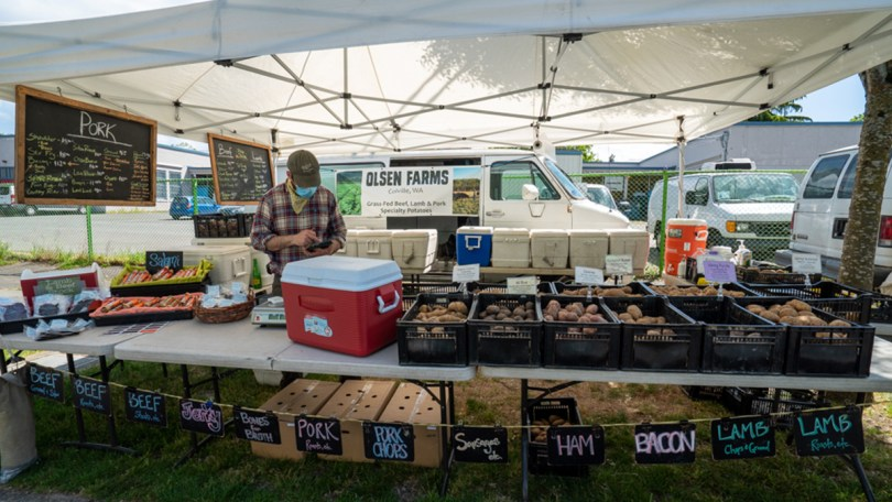 Olsen Farms displays their various offerings from an assortment of potatoes to butchered meats at the Columbia City Farmers Market.