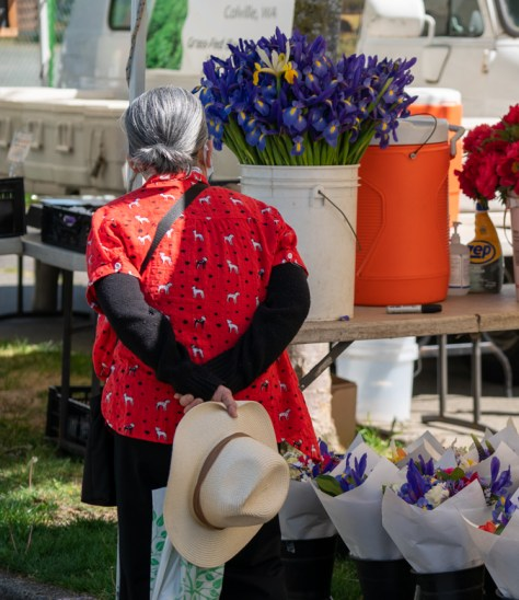 A market-goer browses a booth selling fresh flower bouquets at the Columbia City Farmers Market.