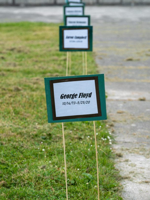"""Photo of a line of placards with the names of people lost to police violence lining the entrance to Martin Luther King Jr. Memorial Park with the first placard depicting """"George Floyd, 10/14/73-5/25/20"""""""