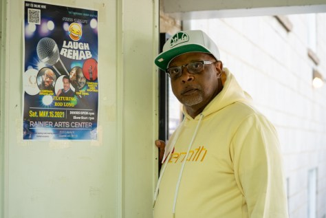 """A Black middle-aged man in a yellow hoodie and white and green baseball cap and glasses stands next to a poster for the """"Laugh Rehab"""" comedy show."""