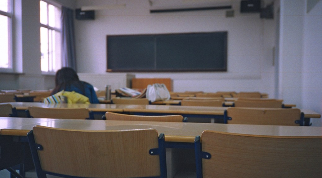 Photo of classroom filled with empty chairs and desks save for one student whose back is to the camera.
