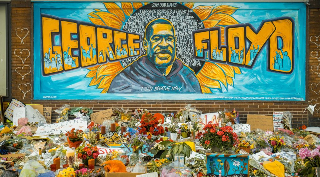 Photo of a memorial to George Floyd in South Minneapolis. A brick wall with a light-blue mural depicting George Floyd in yellows and blacks before a yellow sunflower, his name is also written across the mural in yellow with depictions of light-blue protestors within the letters of his name. Flowers, cards, and other signs are scattered before the mural.