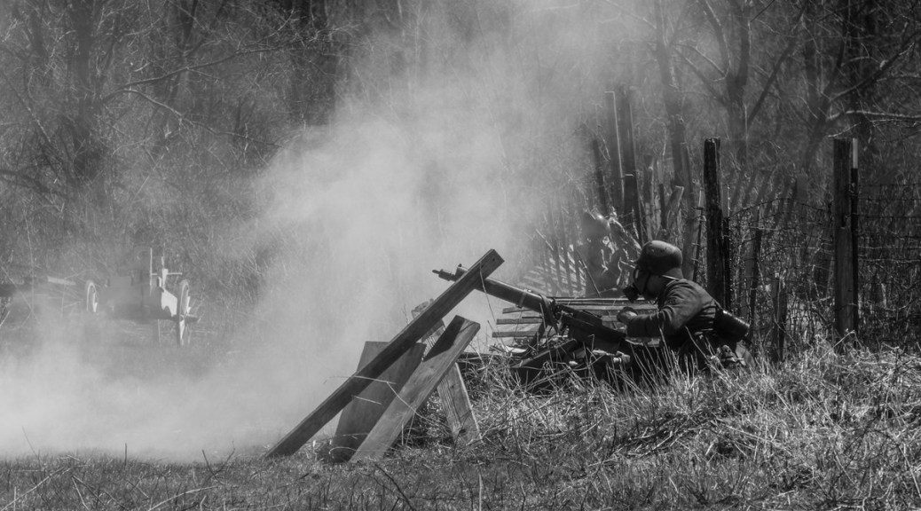 Black-and-white photo of a WWI machine gunner in a trench, smoke rising up behind the gunner.