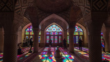Photo of a mosque interior with brightly-colored stained class windows, people mingle and sit to pray.