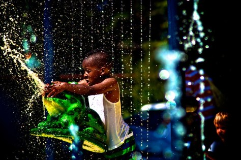 A Black-presenting youth plays at a Seattle-area splashpark.
