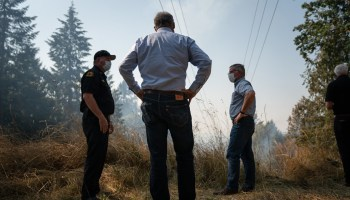 Washington Gov. Jay Inslee stands with firefighters as they survey the scene during the 2020 fire season.