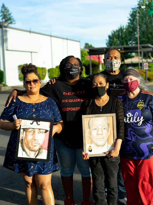 Family members of people killed by law enforcement pose at a vigil for Jesse Sarey commemorating his life and the two years since he was killed by Officer Jeff Nelson.