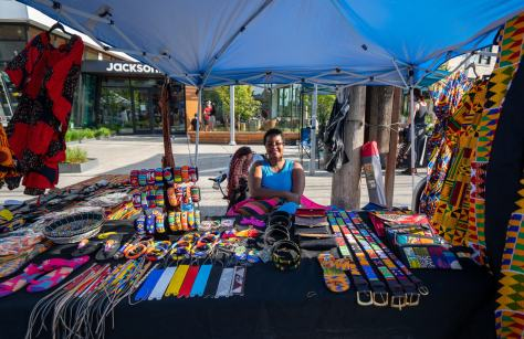 Photo of a Black-presenting, female-presenting individual sitting under an EZ-up tent with tables filled with their colorful wares for sale.