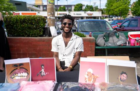 Black-presenting, male-presenting individual sits with his art for sale.