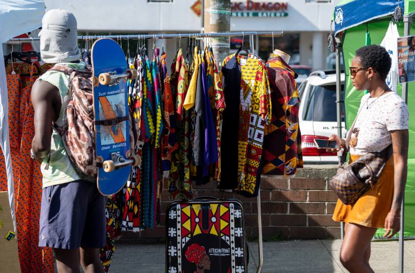 Some people walk by a display of clothes being sold by African Print Takeover.