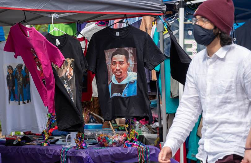 Photo of a male-presenting individual walking past a tented stand selling graphic T-shirts.