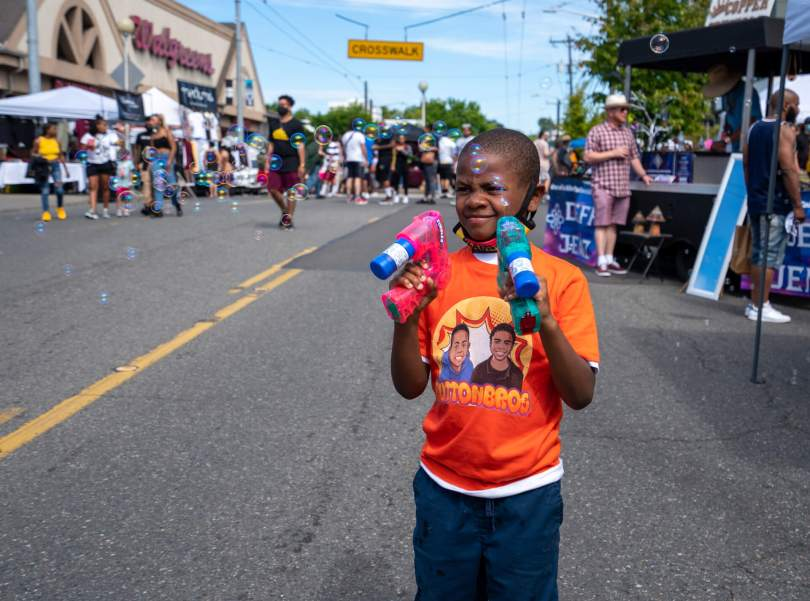 """Photo of a Black-presenting youth in a orange T-shirt that reads """"Button Bros"""" plays with bubbles at """"Honoring Our Black Wall Streets."""""""
