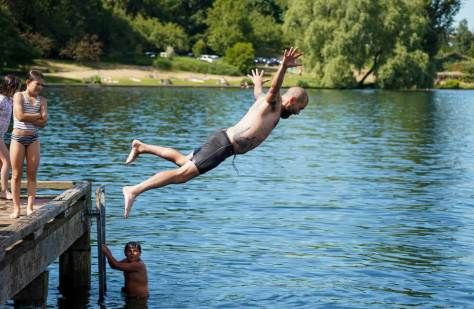 Joshua Dodd leaps into Lake Washington from a pier at Mount Baker Park. (Photo: Susan Fried)