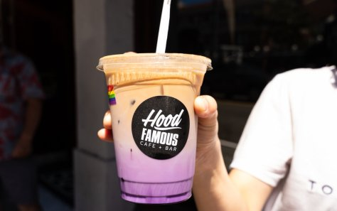 Photo of a purple and beige beverage with a black sticker of Hood Famous Cafe + Bar's logo.