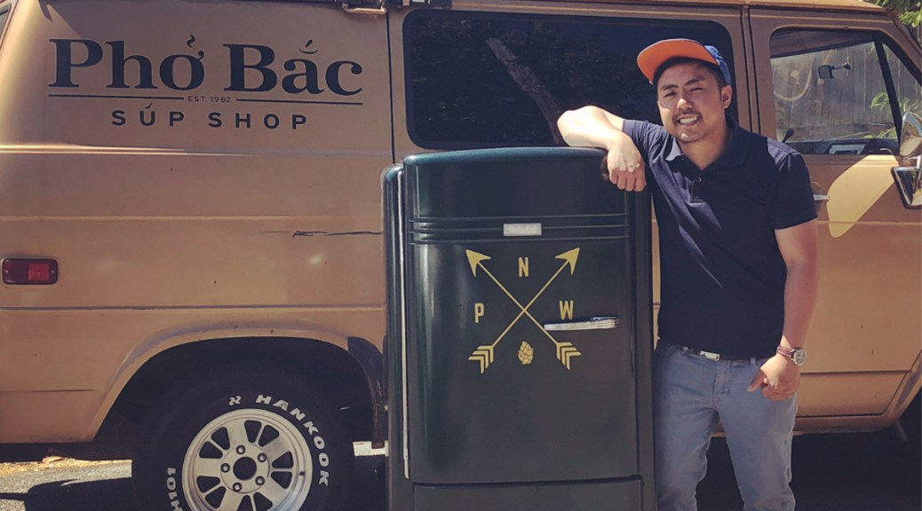 Photo depicting Khoa Pham leaning on a container with a Pacific Northwest symbol in front of a truck with the Pho Bac Sup Shop logo.
