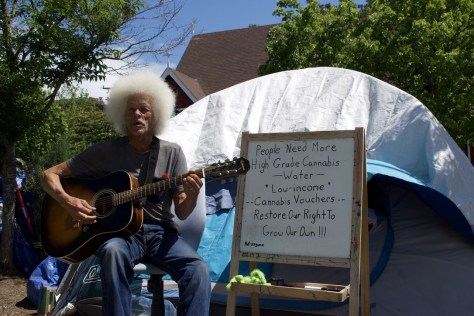 Mr. President teaching guitar lessons outside his tent site at Ballard Commons.