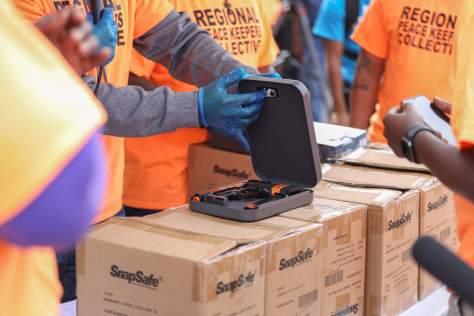 photo of gloved hands showing an open gun safe case