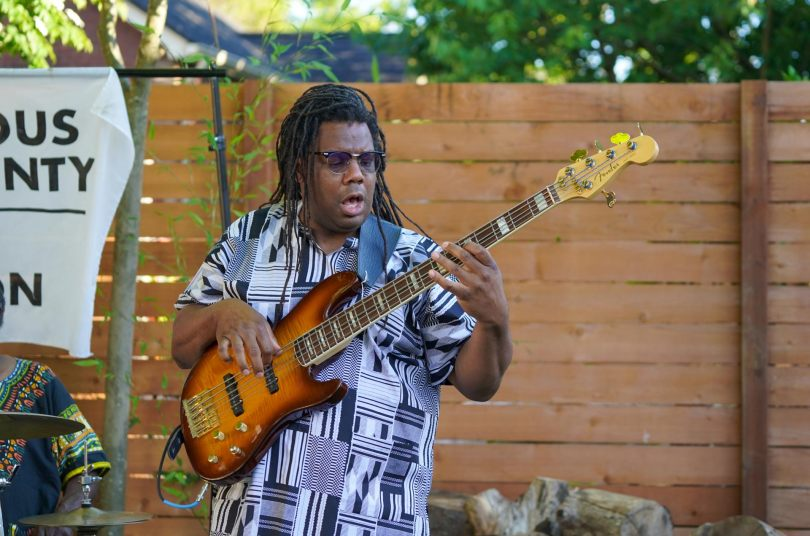Photo of a member of the Blue Meadows Trio playing an electric guitar at Wa Na Wari's Juneteenth celebration.