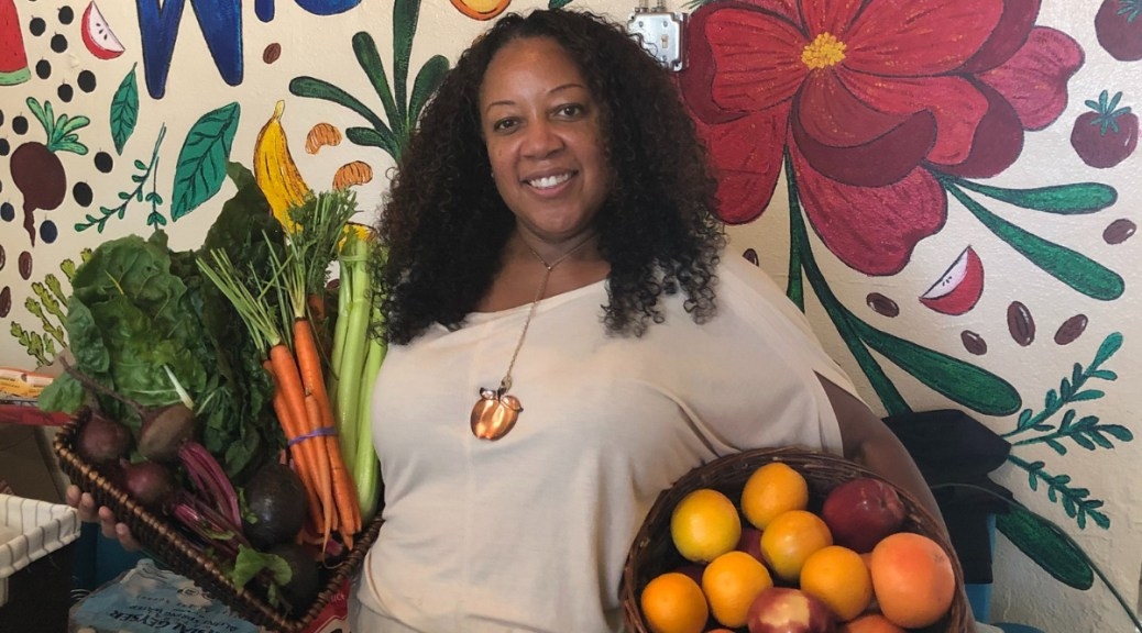 Central Cafe and Juice Bar owner Bridgette Johnson poses with fresh produce in front of a welcoming mural in her cafe.