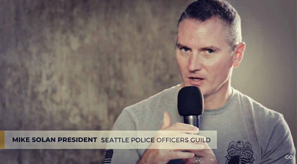 Featured Image: Screenshot of a Converge Media interview with Mike Solan, president of the Seattle Police Officers Guild, in July 2020. On Friday, the Office of Police Accountability found that eight officers, including Solan, violated SPD policy by registering to vote at their precinct address rather than their residences.