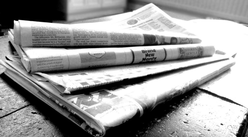 Black-and-white photo of folded newspapers stacked on a table.