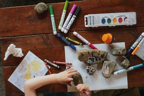 Photo overhead of wooden table filled with rocks, paper, markers, paints and other art supplies. A youth's hands work on painting a rock.