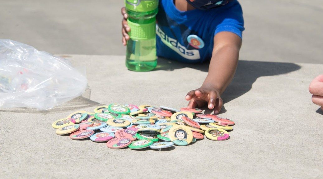 A newly vaccinated youth reaches for a souvenir button at a Vax to the Max event at the ShoWare Events Center.