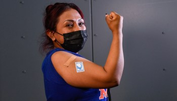 Featured Image: Maria Diaz receives the COVID-19 vaccine. Photo by Marc A. Hermann / MTA New York City Transit, via Flickr published under a Creative Commons license CC BY 2.0.