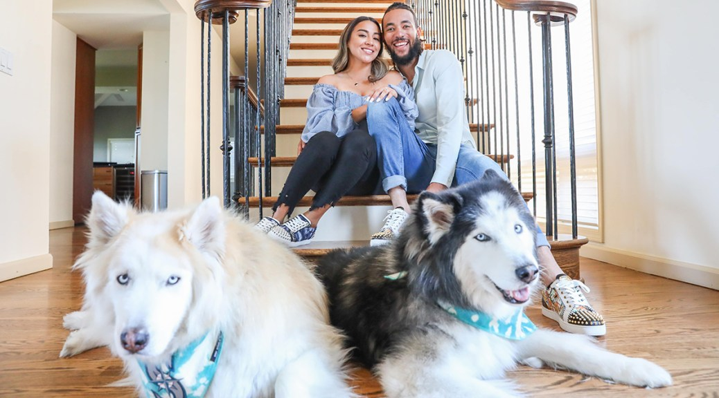 Photo of J.P. Crawford, his wife, and their two dogs sitting in front of a staircase in their Seattle home.
