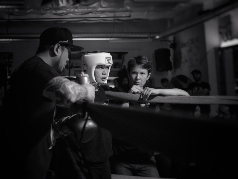 Black-and-white photo depicting a young boxer in the corner of a ring while two coaches offer advice and support.