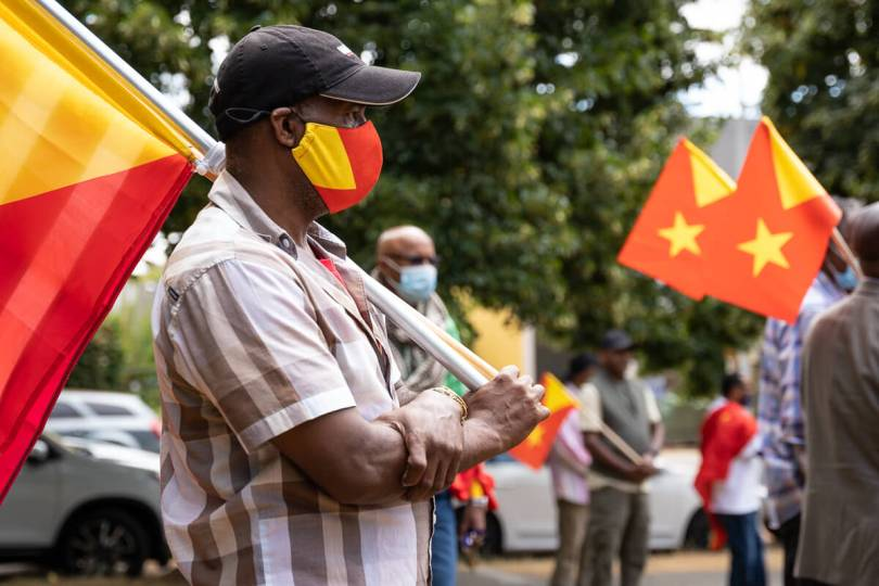A man holds a Tigray flag while listening to a speech during the event.