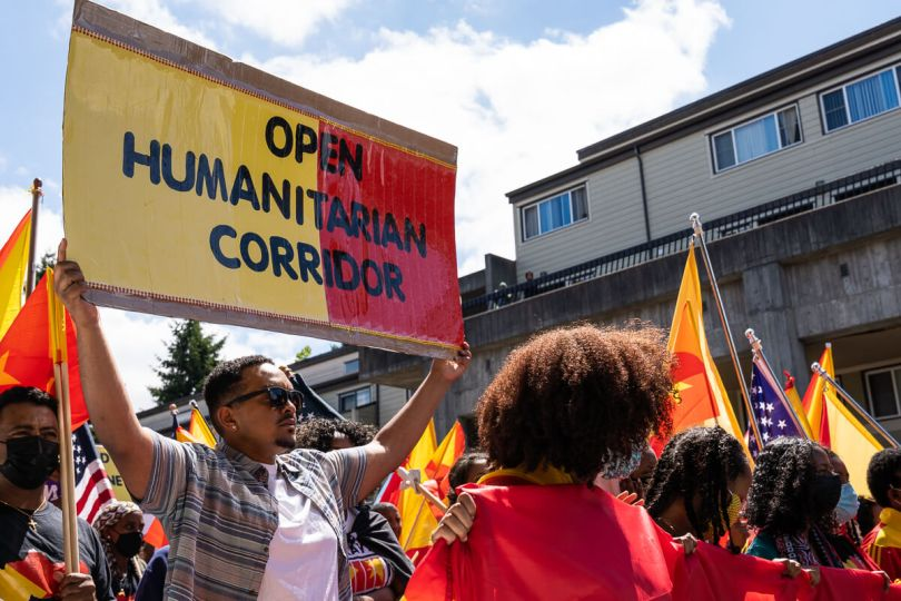 """A protestor holds a sign that reads """"Open Humanitarian Corridor"""" behind local Tegaru youth that led the march."""