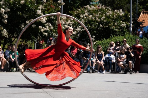 Emma Curtiss performs her choreography with a Cyr wheel in front of a growing crowd.