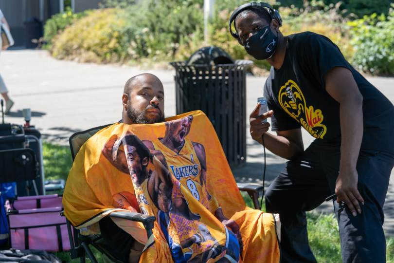 A community barber who donates his services to those in need poses with one of his clients.