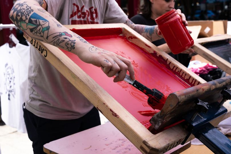 Photo of an individual screen printing with red ink.