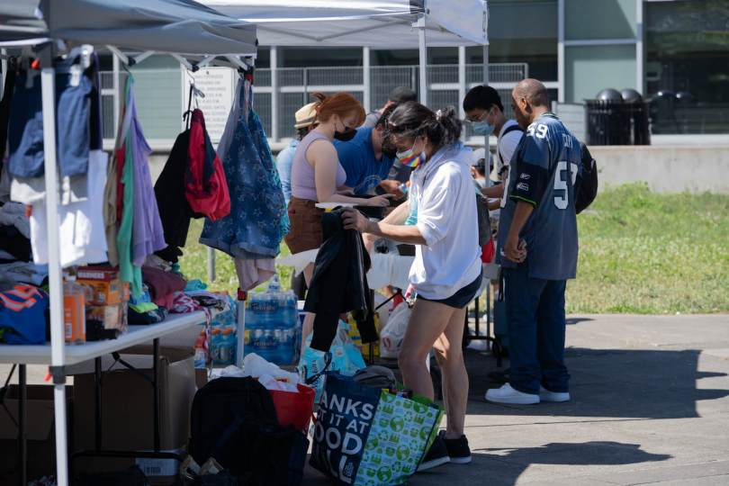 Members of the community look through donations of clothes, food, and medical supplies outside the Rainier Beach Community Center on one of Seattle's hottest days on record.