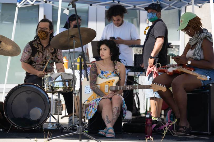 Cody Choi and the band Bananaganz wait to perform at the youth-lead mutual aid pop-up outside Rainier beach community center on one of Seattle's hottest days on record.