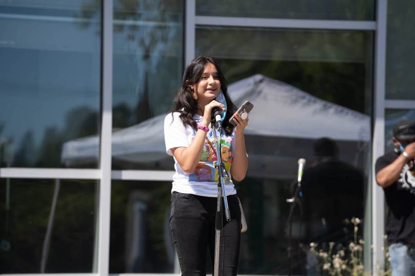 A youth poet performs at the youth-led mutual aid pop-up in front of the Rainier Beach Community Center.