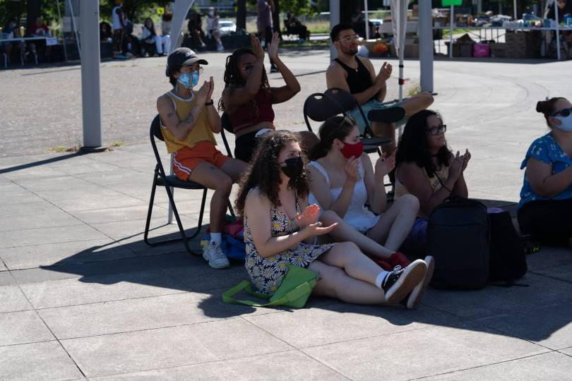 A crowd watching performers stays inside the boundary of a shadow because of the high temperatures on one of Seattle's hottest June days on record.
