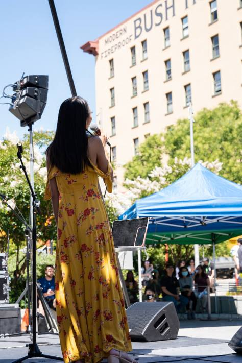 Local artist FRESA performs in front of event attendees at Hing Hay Park.