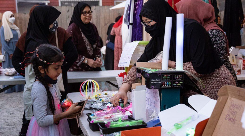 A vendor shows various bracelets to a prospective customer.