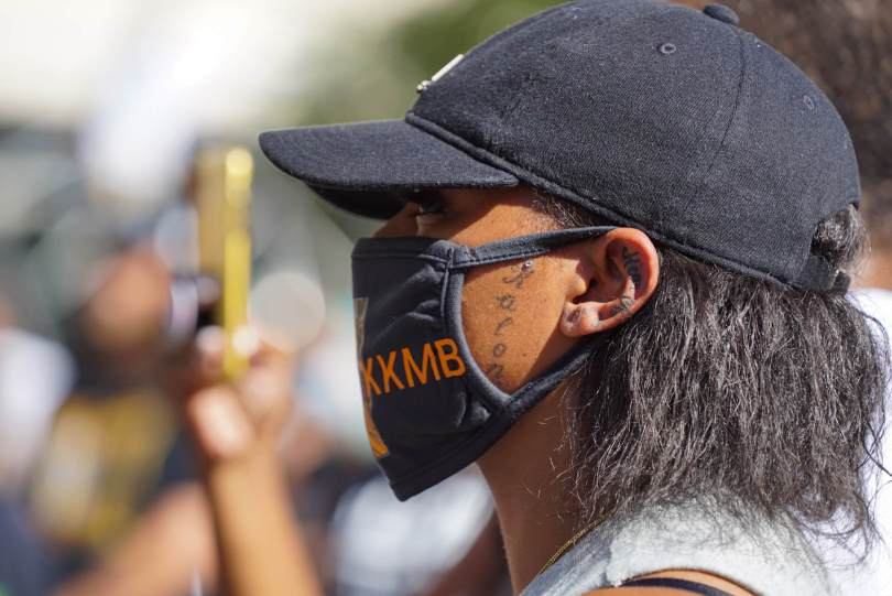 A member of Kaloni Bolton's family listens to a speaker during the #BreatheforKaloni rally on Saturday, July 24, 2021, at Westlake Park.