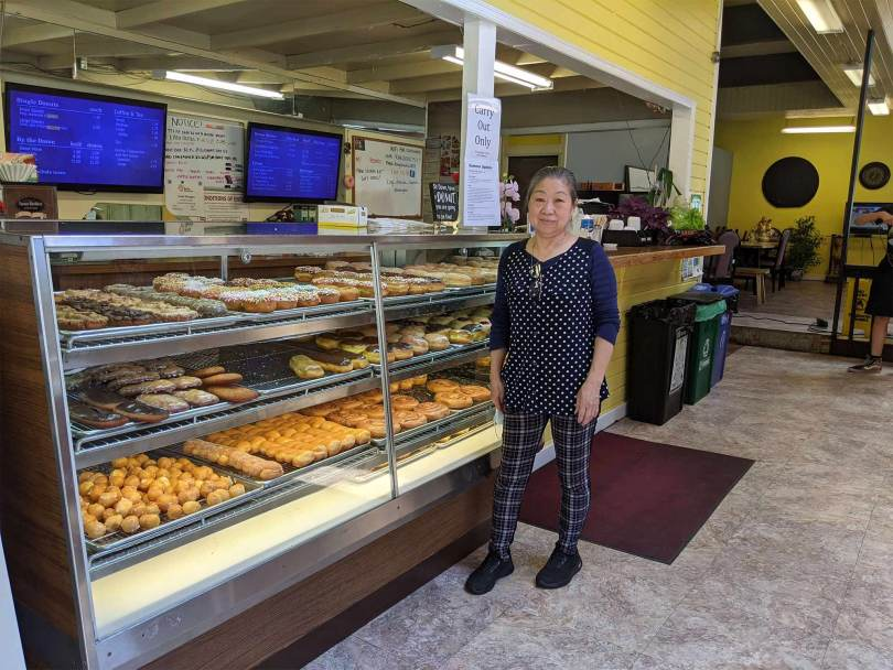 Photo of Kim Sok standing beside the case of donuts in King Donuts
