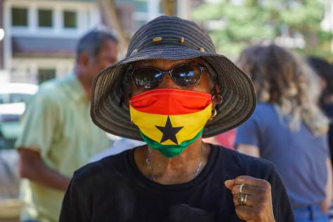 A community member wearing an Ghana National Flag mask reacts to one of the speakers during the Rally
