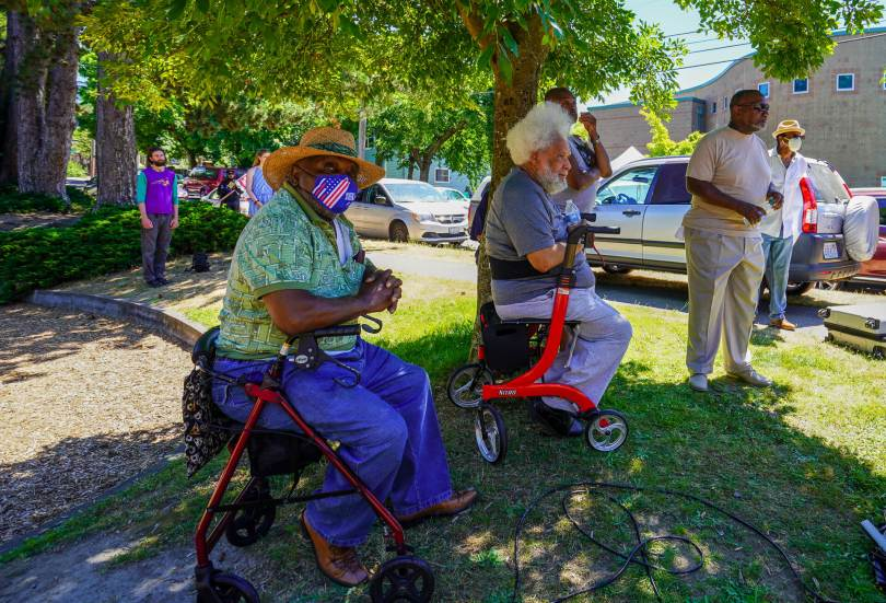 Community members listen to speeches during the rally under the shade of a tree.