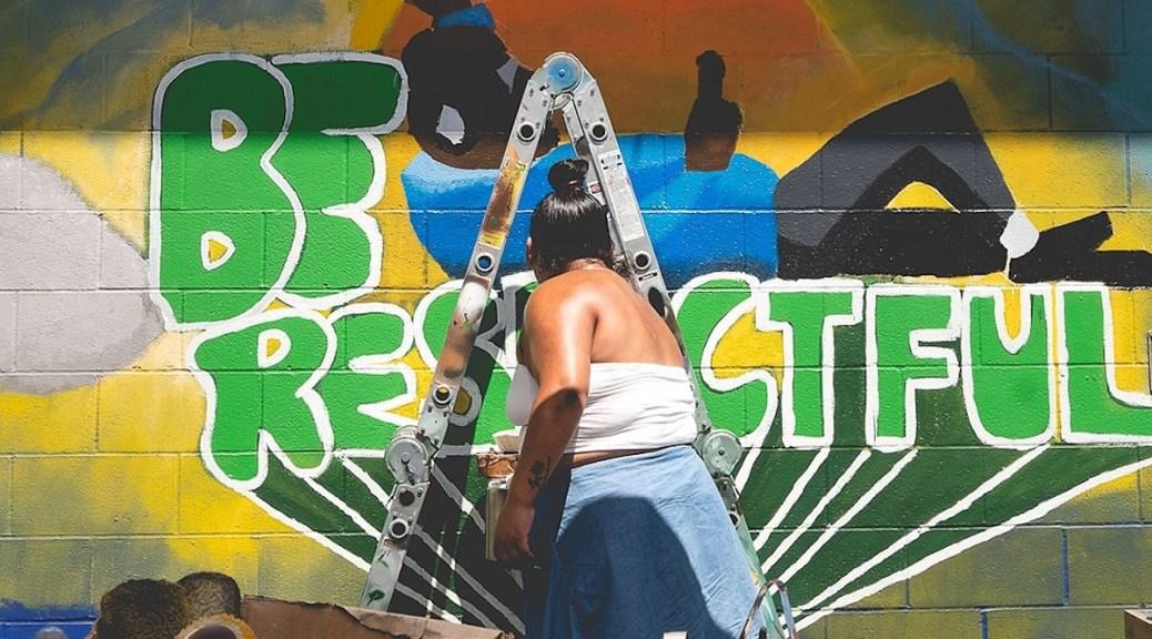 A member of the Rainier Beach Action Coalition helps paint a community mural at Be'er Sheva Park (Photo: Britt Lê )